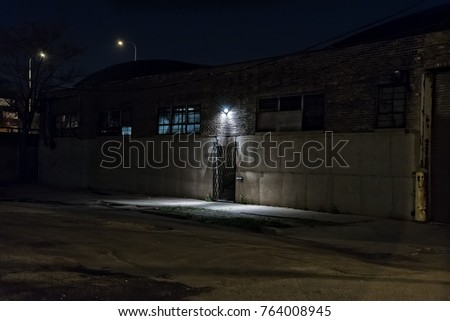 Dark scary alley at night with gated door warehouse entrance.