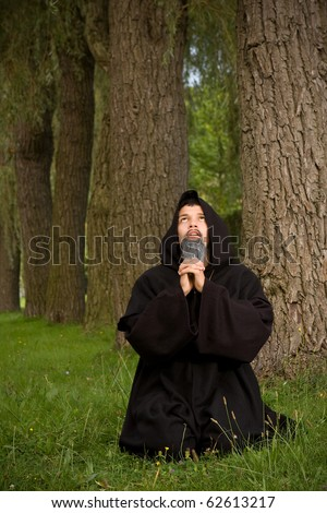 Dark scene of a black hooded monk praying in the woods