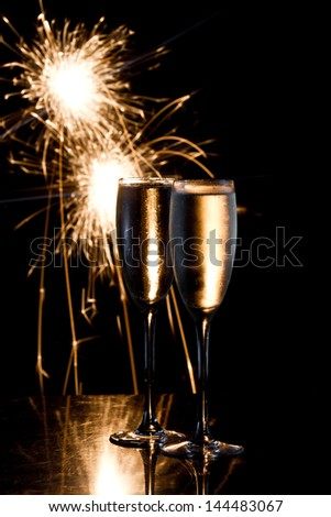dark scene with two glasses of champagne and fireworks in the background