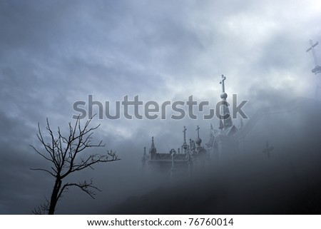 Dark scenery with clouds, fog, dead tree and cemetery (added some digital noise) - stock photo