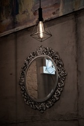 Dark sepia photo of lampshade on cement wall background with defocused antique ellipse shape mirror in vintage ornate frame and blurry reflection in mirrored surface. Retro interior decoration.