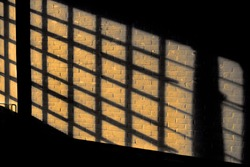 Dark shadow on a stonework wall illuminated by golden sunlight - concept dramatic contrast film noir mystic interior texture background surface structure window close up detail evening sunset sunrise