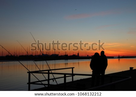 Dark silhoette of two fishermen with fishing rods on the pier, at sunset, with many silhoettes of yahts/boats on red sky with transition upward to blue, as a background. #1068132212