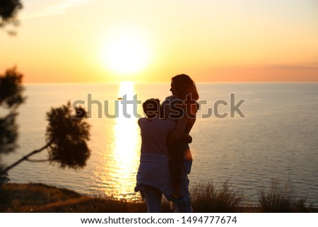 Dark silhouette Mom and daughter at sunset by the sea beautiful view and water and the gradient of the sky