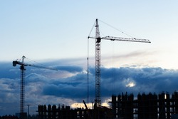 Dark silhouette of a construction crane, dark blue cloudy twilight sky. Construction of a residential building, evening industry