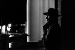 dark silhouette of a man in a raincoat with a hat and a scar on his face at night in a crime Noir style