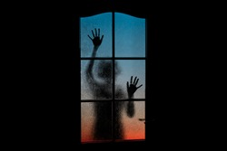 Dark silhouette of girl alone in isolation on light background behind closed glass door. Abstract image of sadness, sorrow, apathy, depression, melancholy. Girl locked up in depths of subconscious.