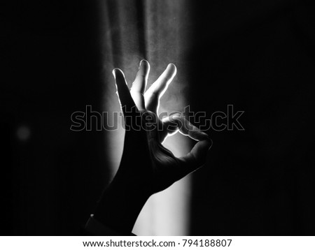 dark silhouette of human male hand with fingers in spotlight or backlight light with okay or ok gesture on black background with dramatic projector shine ray or beam #794188807
