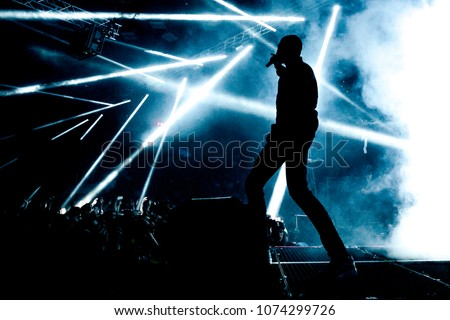 Dark silhouette of singer in the stage. Light rays and smoke in the background. Energetic performance.