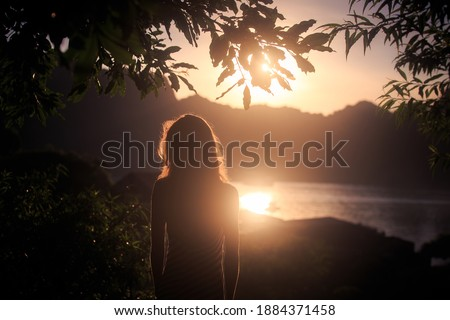 Dark silhouette of slim woman standing on tranquil ocean beach at bright sunset light. Tropical vacation concept