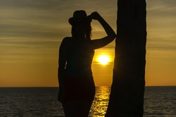 Dark silhouette of the girl against the sea