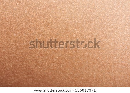 Dark skin of woman hand macro. Human skin texture background #556019371