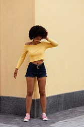Dark-skinned African girl in yellow top and blue shorts against the yellow wall