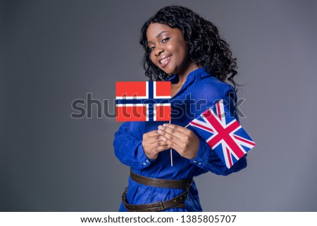 Dark-skinned beautiful woman a gray jacket with dark curly hair posing on a gray background. And holds the British and Norway flags in her hands and smiles.