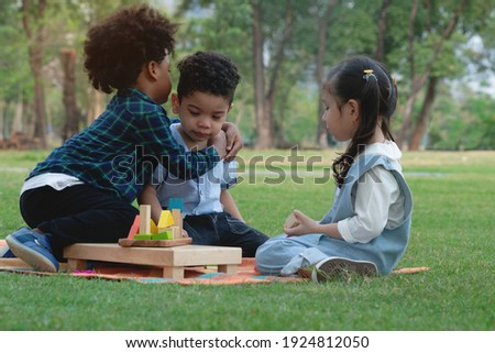 Dark skinned boy hugged and comforted his little friend, group of multi-ethnic kids in park, little girl looked closely, warm relationship between children Foto d'archivio ©