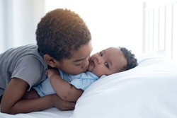 Dark skinned brother expressing love for his little baby sister at bed room, adorable sister and brother portrait, childhood relations concept