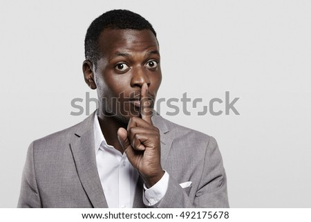 Dark-skinned entrepreneur in gray suit holding finger on his lips, asking to keep confidential information private, concealing commercial secret, saying 'hush'. Black boss asking employees to be quiet