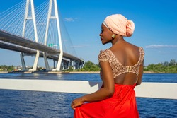 Dark-skinned girl in an open dress. African-American woman walks through the city on a Sunny summer day. Dark-skinned girl posing in profile. African-American woman on the background of the bridge.