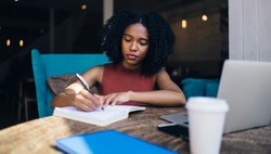 Dark skinned hipster girl writing information in knowledge notepad while sitting at table with modern technology for research and e learning, African American female student preparing to exam