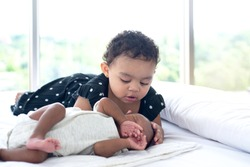 Dark skinned little sister looks with adoration at little brother, cute girl and new born baby boy relax in a white bedroom. 15 days year old, dark skinned newborn at home, selective focus