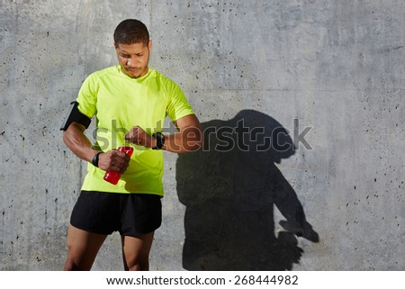 Dark-skinned male athlete in fluorescent t-shirt holding a water bottle looking tired and exhausted, sporty young man resting after workout standing on concrete wall background at sunny afternoon