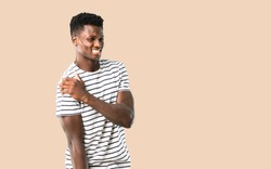 Dark skinned man with striped shirt with shoulder pain on isolated ocher background