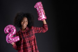Dark-skinned teen girl holding  metallic pink number balloons on Black background, number two and one shaped balloons