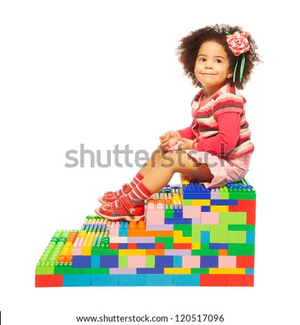 Dark skinned two years old girl on the stairs maid or toy plastic blocks