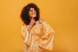 Dark-skinned woman in sunglasses smiling on isolated backdrop. Pensive girl in summer clothes posing on yellow background..