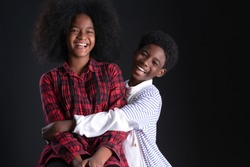 Dark skinned younger brother hugging with smiley face beside of his older sister, on Black background