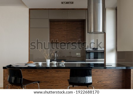 Dark, small and modern kitchen with wooden style furniture, black countertops and kitchen island with induction hob under new silver kitchen hood and two, black chairs