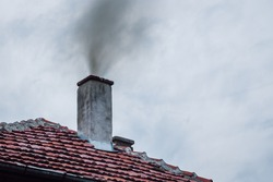 Dark smoke coming out of the chimney of a house in winter. Concept for environmental pollution, heating with solid fuel.