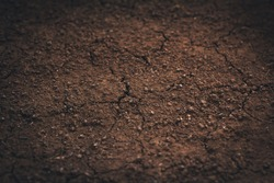 Dark soil texture closeup of dry soil background