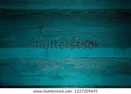 Dark stained blue teal reclaimed wood surface with aged boards lined up. Wooden planks on a wall or floor with grain and texture. Stained vintage wood background.