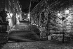 dark stairs with two statues enlightened historical lanterns in black & white design