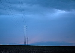 Dark storm clouds and orange evening glow over the fields with pylons and electricity wires in Munkzwalm, Flanders, Belgium