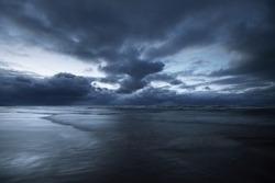 Dark storm sky above the Baltic sea, waves and water splashes. Dramatic cloudscape. Nature, environment, fickle weather, climate change. Atmospheric scenery. Panoramic view, long exposure