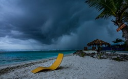 Dark stormy clouds gather over a tropical island with an idyllic white sand coastline. Raging monsoon closes in on a picturesque exotic island in the Maldives. Tropical rainstorm brings big waves.