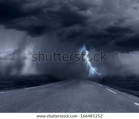 Dark stormy clouds over road