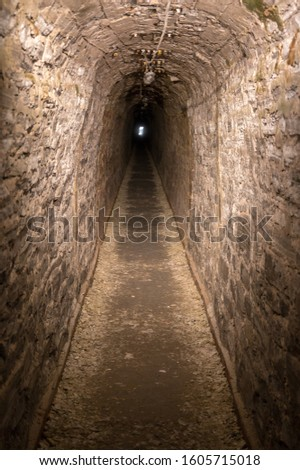 Dark straight cave with light at the end of the tunnel as a metaphor for hope and perseverance