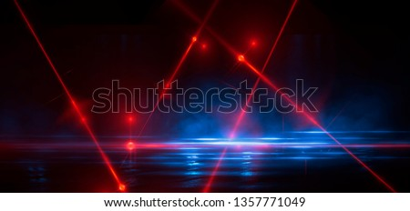 Dark street, reflection of neon light on wet asphalt. Rays of light and red laser light in the dark. Night view of the street, the city. Abstract dark blue background.