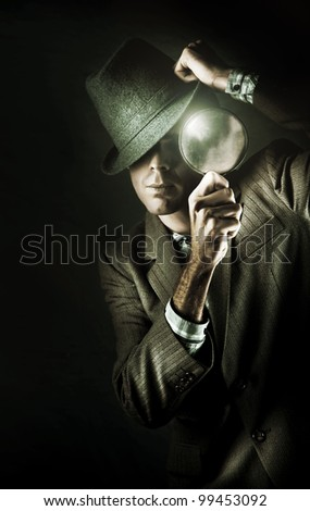 Dark Studio Photo Of A Mystery Man Wearing Retro Business Fashion While Examining A Clue Of Evidence Through A Eye Glass In A Undercover Spy Concept