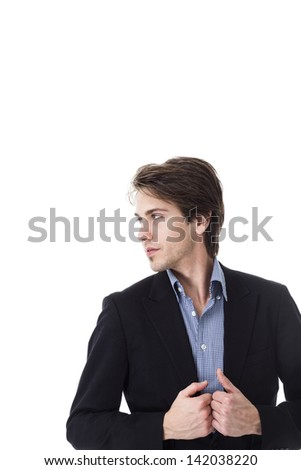 Dark studio portrait of a serious man standing in the shadows with his arms folded and a pensive expression