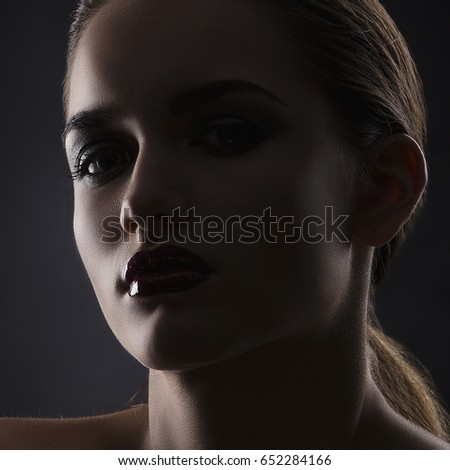 Dark style beauty portrait of young girl with bright makeup, red glossy lips and perfect fresh skin and hands near head. #652284166