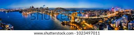 Dark Sydney city CBD landmarks around Sydney Harbour connected by Sydney Harbour bridge and bright cahill expressway illuminated and reflecting in water.