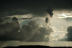 Dark thunderclouds pierced by the rays of the sun.