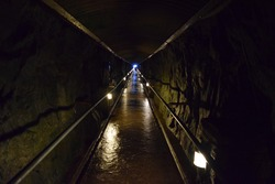 Dark underground tunnel in a mountain leading to an exit