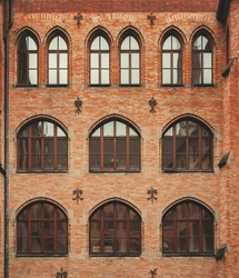 Dark vintage clean brick factory wall with rounded windows. Industrial background. Loft inspiration. Construction facade concept. Vintage effect.