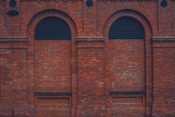 Dark vintage clean brick factory wall with two rounded sealed windows. Industrial background. Loft inspiration. Construction facade concept. Vintage effect.