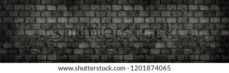 Dark wall. Old and weathered grungy black dark gray concrete block brick wall texture background with holes and cracks with vignetting in a large panoramic wide banner background